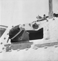 The driver of a Grant tank takes a closer look at a gouge in the armour plate made by a 50mm anti-tank round, Libya, June 1942.