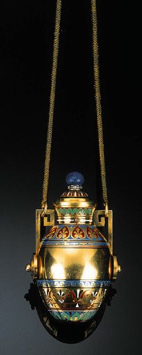 A MID 19TH CENTURY POLYCHROME ENAMEL, GOLD AND GEM-SET PERFUME BOTTLE:  Modelled as an urn, the tapering ovoid yellow gold body decorated with concentric multi-coloured enamel designs, the domed hinged stopper with similar decoration and lapis lazuli bouton terminal above a band of rose-cut diamonds, the handles of a Greek key design, the whole suspended from a snake link chain, French control marks, 7 cm high