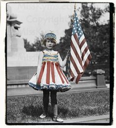 Vintage hand-tinted photo of a little girl dressed as Lady Liberty for the Fourth of July. Flapper style, 1920s.