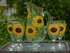 Elegant footed pitcher IN X IN) and four footed goblets hand-painted with sunny golden sunflowers and deep green leaves. Lovely for entertaining and an excellent wedding and show