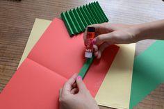 Jednotlivé proužky vystřihneme a poskládáme do harmoniky. Postupně přilepíme k oběma stranám papíru.