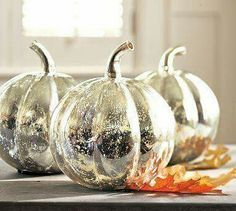 Dollar Store pumpkins, paint white, spray with Krylon Glass Spray for a mercury glass look. Need to try this.