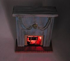 Blue Shabby Chic fireplace with flickering fire. Includes battery, andirons & grate, logs. 1:12 inch scale.  Hand made in USA.