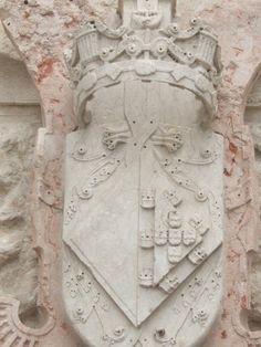 Brasão da Infanta D. Maria de Portugal na fachada sul da igreja, junto à milagrosa fonte