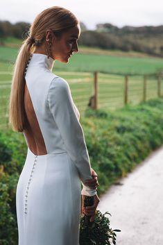 Sensuous high neck, backless, long sleeve wedding dress by Andrea Hawkes. Bridal ponytail. Nikki Witt Madonna cross earrings. Photography Joanna Bongard. #backlessweddingdress #andreahawkes