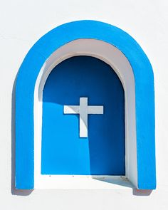 Chapel window in mountains Asfendiou, Kos, Greece - We hiked a mountain trail near Asfendiou, Kos, Greece. We saw a little white chapel, hidden in olive gardens. In one of the 'windows' was this roman-orthodox cross, in the for Greece so typical white and blue color setting.