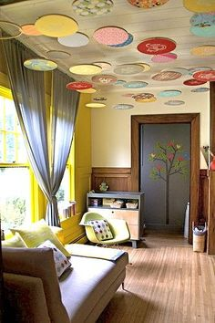 Creative idea using wooden embroidery hoops (purchase at a craft store) and place colorful fabric in the hoops. Since these are light weight decorating items the hoops are perfect to hang from the ceiling or on the wall. Nursery by Lorena & David of San Francisco.