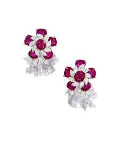 Pair of ruby and diamond earclips. Each flowerhead set with oval and cushion-shaped rubies and marquise-shaped diamonds, further decorated by brilliant-cut stones, mounted in white gold.
