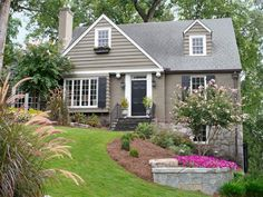 Cape Cod style -- house colors & landscaping - retaining walls of stone, brick or concrete can shore up the layers of a sloping yard & define flower beds: main bed, bordered by a granite retaining wall, is filled w/ purple 'Wave' petunias; fountain grass grows near the large front window. Crepe myrtles bloom all summer long & are beautiful & low-maintenance - HGTV