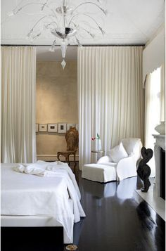 A wall of white cloth and a floor that mirrors bed like water.