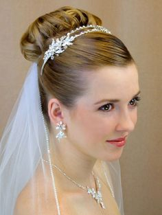 Veil and hair concept.  Hair up in a distinctive bun, something pretty surrounds it, gathered tulle attached below bun.  No rinestone edge to the veil, no coming over shoulders.