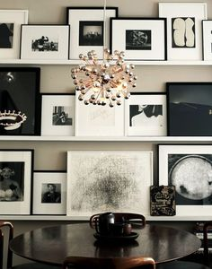 Propping black and white photography on a shelf is a relaxed, casual way to approach a gallery.  Wood of shelves to match fireplace facade.