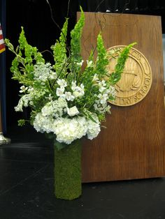 Commencement ceremony flowers for the podium in moss cylinder would work equally well as altar arrangements.