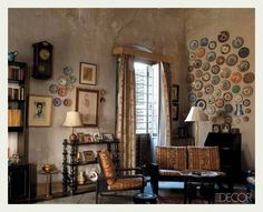 bare walls - not usually a popular choice; but here they are a perfect display for the variety of antique plates, pictures, and upholstery.