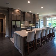 Kitchen For A Large Gathering   ProSource Wholesale    Reclaimed wood, arched doorways and nail trim barstools give this craftsman kitchen an extra dose of warmth and texture.