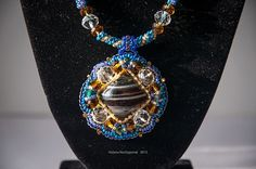 Pendant is made in blue and brown tones from the Czech beads Preciosa. It is also used Czech crystal and natural agate stone in the form of a square.  Dimensions: Pendant: 6h5sm Harness: 43 + 8cm Weight: 47gr  Materials: Czech crystal, Czech glass beads preciosa, natural agate, felt, suede accessories.  $ 16.50