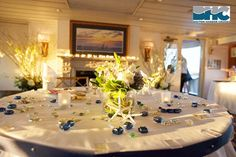 Decorations including starfish, sea glass, blue candles and more, add to the ambiance of a nautical wedding table.
