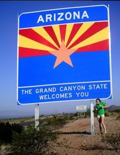 Maddie poses at the Arizona State Line on our Road Trip to the Grand Canyon!
