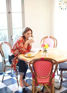 """""""Every girl needs a little bit of Paris with her! Maya wanted some brightness to go with the black and white floor in the kitchen, so she chose French bistro chairs in a variety of colors. The table is vintage and the clock is from Design Within Reach."""