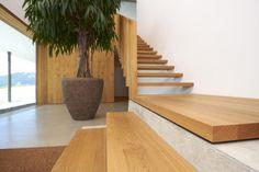 Wooden staircase inside Haus B by Architektur + Raum.