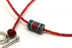 red pearlized seed beads and polymer clay bead with heart ...pretty!