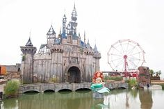 The dismaland castle with the little mermaid infront. The mermaid is by Banksy