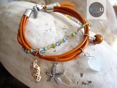 Bohemian - Orange leather bracelet with suede tassel and a row of seed bead - Clear blue sea glass, pewter, pottery piece and roller shell - 64.95$ - See this unique piece on seaucollection.com