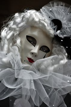 This Venetian mask has a decorative beauty mark and a teardrop, black and white with glossy curls.