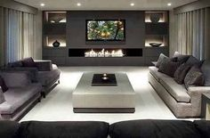Love this fireplace. Sleek and modern with lit up alcoves for art. TV does not detract.