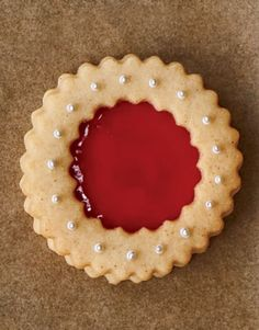Heat, then strain, preserves, or use jelly for a clear, gemlike effect. Slightly cool for smoothest application. Add sugar, nonpareils, or dragées before baking; gently press into dough to help adhere. Spread a thin layer of jelly on the base cookie and on the back of the top cutout cookie. Lightly press the cookies together. Fill the cutout area to the top of the cookie edge with jelly. Recipe: Sugar Cookie Dough   - CountryLiving.com