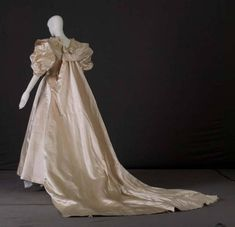 Wedding gown, 1935. Silk satin, crepe Dress, wedding-style, of off white silk satin. High neck with wide neckline and fold-over Peter Pan collar. Off-white silk crepe at collarbone. Fitted bodice. Pleated sash. Voluminous wing-shaped elbow-length sleeves. Full, floor-length skirt; long train attached to back of neck and at skirt.