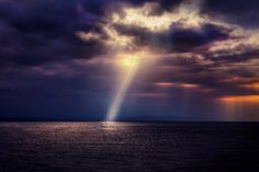 a boat floating on sea water with sunlight shining through dark clouds,Night, sea, ship, sunset, impressive shot of nature, amazing picture, beautiful