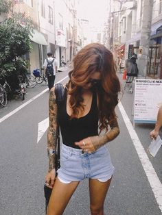 Black Leotard, High Waist Light Wash Denim Short Shorts, Sleeve Tattoo, Sunglasses, Long Strap Black Bag, Bangle, Curled Red-Brown Hair.