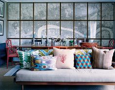 Designer Ben Pentreath's London apartment: A sofa found on eBay decorated with cushions from Pentreath's shop in front of a map of Londo
