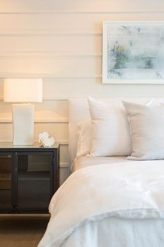 A light blue abstract art piece hangs from a shiplap wall over a white slipcovered headboard accenting a bed dressed in soft white bedding while a black industrial cabinet sits beside the bed lit by a white table lamp in this restful cottage bedroom. Slipcovered Headboard, White Headboard, White Bedding, Wall Headboard, Blue Accent Walls, Accent Wall Bedroom, Home Bedroom, Bedroom Decor, Master Bedroom