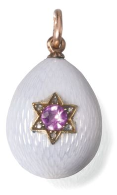 A Fabergé gold and enamel egg locket, workmaster August Hollming, St Petersburg, 1904-1908 | Lot | Sotheby's -enamelled in translucent white over hatched grounds, the front and back set with simulated pink and blue sapphires within six pointed stars of rose-cut diamonds, the interior with two glazed apertures, struck with workmaster's initials, 56 standard, scratched inventory number 3037 height 2.2cm, 7/8 in.
