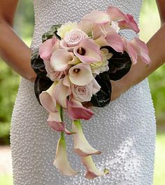 The FTD® Pink Cascade™ Bouquet exudes pure elegance and feminine charm. Pale pink mini calla lilies, roses and dahlias are arranged in a cascade style and accented with a white taffeta ribbon to creat