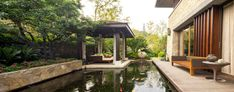 Quiet backyard pond featuring colorful red and yellow Koi fish, surrounded by red flowers and greenery, and with access to a nice gazebo: perfect for entertaining guests, or just for a relaxing evening with the family.