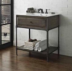 """Toledo blends a clean-lined profile with machine age details in a modern approach to bath décor. Decorative """"rivets"""" on cabinet and mirror provide a chic, cutting edge industrial look. Highlighting the innate beauty of the wood is a sand blasted Driftwood Gray finish, perfectly complemented by Charcoal finished metal framework and antique brass finished hardware. …"""