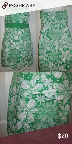Strapless dress Green & white flowered strapless dress.  Has buttons, a flower and 3 layers of scalloped edge on the front of the drrss.  It also has a side zipper and elastic located in the back top. Length from back,top to bottom is 22 1/2 inches. Dresses