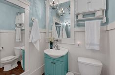bathroom with white wall, white toilet, white wooden framed mirror, turquoise cabinet of Much Storage to Your Need and Liking in Tiny Bathroom