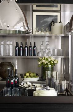Modern and clean open-shelf kitchen storage housing Ralph Lauren Home essentials: Sackett barware and Asher porcelain serving pieces with black leather handles.