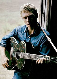 Steve McQueen playing guitar photographed by Paul Popper, 1965.