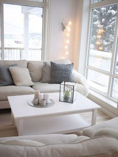 A grey and white themed room with a sofa, some scatter cushions and some fairy lights strung on some faux antlers