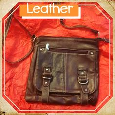 "NWOT. Leather Satchel/Crossbody Bag Leather satchel/crossbody bag. Dark burgundy in color. 10"" in width. 9"" in height. Adjustable strap goes to 27"". Cool Buckle accents an front. Has one zipper on the front, one zipper on the back. Nylon interior. Interior has 2 pockets on the inside and a zipper compartment. Pristine. Bags Crossbody Bags"