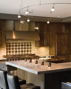 Don't you love this contemporary kitchen with MonoRail Lighting?  The Satin Nickel rail from Tech Lighting follows the bar. It has Bee functional art lights and Mini Om heads.