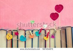 Valentines day concept. Many multicolor crochet hearts on books over pink background.