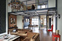 Ambiente integrado, em estilo industrial com decoração sofisticada. A sala de estar, decorada com conjunto de sofá marrom, se estende até a sala de jantar e escadaria que leva ao mezanino no interior do ambiente todo aberto.