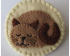 Felt Cat brooch/Pin This cat brooch has been hand made from felt and is 5 cm diameter. It has silver sequin stars and a silver safety brooch fitting stitched on to the back. For cat lovers or a cat lovers gift which is small enough to slip inside a greetings card.