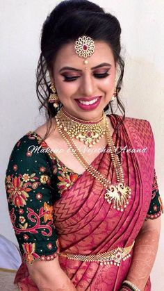 Pretty in pink! Nandita is all smiles after her bridal makeover for her reception. Hair and makeup by Vejetha for Swank. South Indian bride. Indian bridal makeup. Berry lips. Eyemakeup on fleek. Bridal hairstyle. Saree blouse design. Bridal silk saree. Bridal jewellery. Maang tikka. #GoldJewellerySouthindian